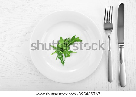 Arugula leaves in plate with fork and knife on wooden table, top view - stock photo