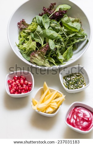 Arugula salad with pomegranate seeds and sauce, pesto sauce and freshly cut avocado in bowls on white background - stock photo