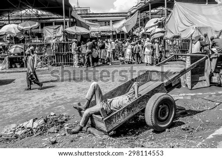 Arusha, Tanzania, Africa - January 2, 2013: Man lying on a wooden cart sleeps at the market in town - stock photo