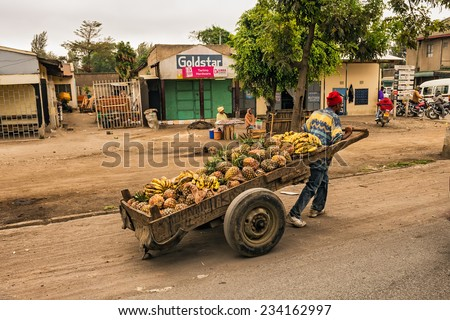 ARUSHA, TANZANIA - OCTOBER 21, 2014 : African man pulling a cart full of fruit in a shopping street of Arusha - stock photo