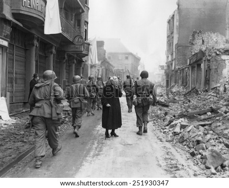 As infantrymen march through a German town, a shocked old woman stares at a the ruins. March-April 1945. Germany, World War 2. - stock photo