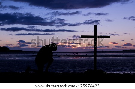 As the day ends a man kneels in pray before a cross. - stock photo