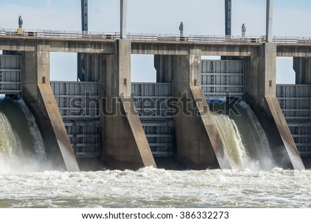 As the river's water flows across the hydroelectric generator rotors, electrical power is produced.The power is then conditioned at the power house. It is then routed by power poles to several states. - stock photo