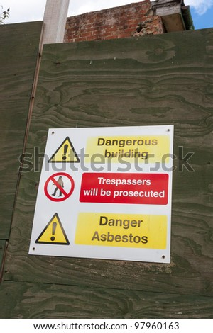 Asbestos Danger Sign calls attention to a hazardous building. - stock photo