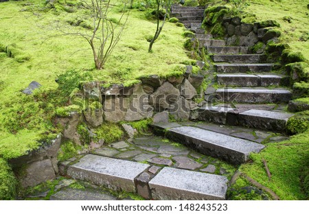 Ascending Curved garden stone stairs bordered with green moss - stock photo