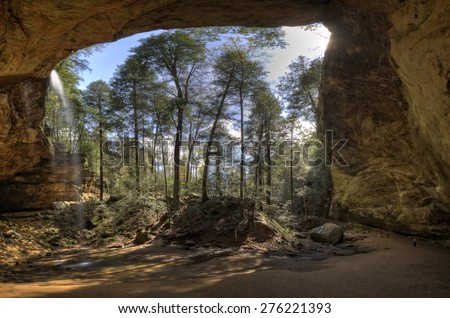 Ash Cave waterfall panorama.  This is the largest  recess cave in Ohio.  In the lower right you can see some people which gives you an idea of the scale of the cave. - stock photo