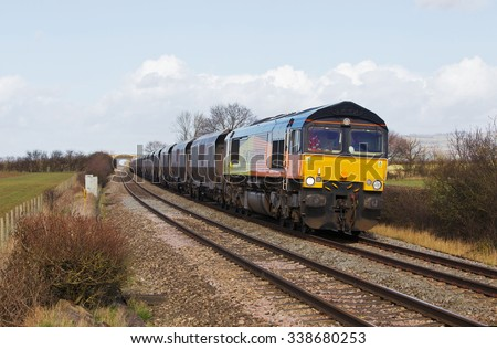 ASHCHURCH, UK - FEBRUARY 27: A Colas operated freight train heads toward Bristol with an empties return rake on February 27, 2014 in Ashchurch. Colas operate a fleet of approx.16 locos across the UK - stock photo