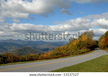 Asheville North Carolina's beautiful view of the Blue Ridge Parkway during the Autumn.    Blue skies, white clouds and colorful trees.  Road disappears into the foliage. - stock photo