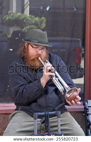 Asheville, North Carolina, USA - April 9, 2014:  A male street musician sits on a sidewalk and plays his trumpet for tips on on April 9, 2014 in downtown Asheville, NC - stock photo