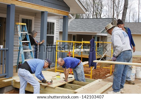 ASHEVILLE, NORTH CAROLINA, USA - APRIL 3, 2008: Volunteers for the nonprofit organization Habitat for Humanity work building new energy efficient houses for low income partner families in Asheville. - stock photo