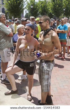 ASHEVILLE, NORTH CAROLINA, USA - AUGUST 25, 2013: A crowd gathers by a young topless woman who is accompanied by a young man wearing a bra at the Go Topless Rally in downtown Asheville   - stock photo