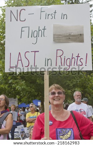 Asheville, North carolina, USA - August 4, 2014:  A woman holds a sign protesting North Carolina's lack of rights on August 4, 2014 at a Moral Monday rally in downtown Asheville, NC - stock photo