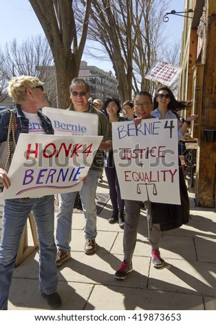 Asheville, North Carolina, USA - February 28, 2016:  An enthusiastic and diverse crowd of Bernie Sanders supporters march down an Asheville street holding signs during a political rally - stock photo