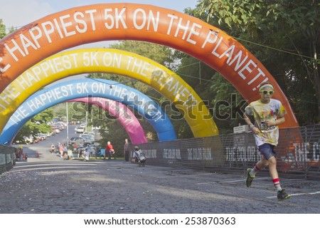 Asheville, North Carolina, USA - July 26, 2014:  A young male runner covered in colorful dye nears the finish line as he races in the 5K Asheville Color Run on July 26, 2014 in Asheville, NC  - stock photo
