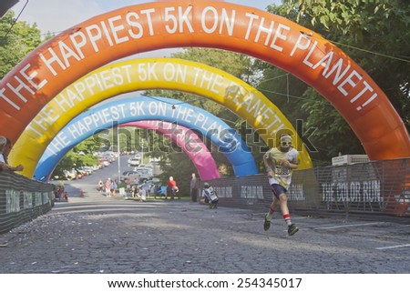Asheville, North Carolina, USA - July 26, 2014:  A young male runner covered in colorful dye nears the finish line as he races in the 5K Asheville Color Run in downtown Asheville, NC  - stock photo