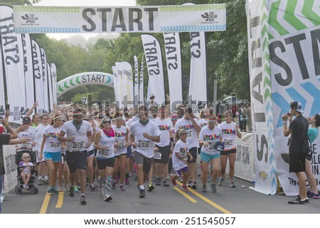 Asheville, North Carolina, USA - July 26, 2014: Color Run Runners of all ages and genders wearing colorful t-shirts and headbands enthusiastically take off from the starting line as the race begins - stock photo