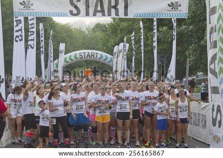 Asheville, North Carolina, USA - July 26, 2014: Excited Color Run racers about to take off from the starting line on July 26, 2014 in downtown Asheville, NC C - stock photo