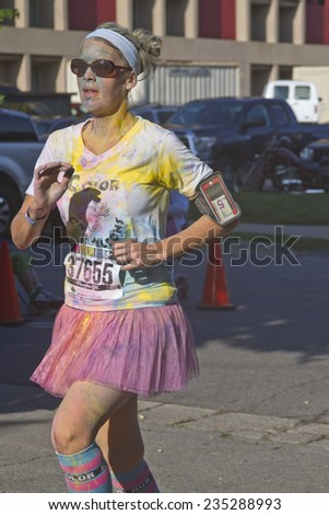 Asheville, North Carolina, USA - July 26, 2014:  Woman runner wearing a tutu splattered with colorful dye races in the the happy Asheville 5K Color Run on July 26, 2014 in downtown Asheville, NC