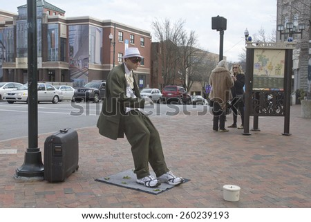 Asheville, North Carolina, USA - March 2, 2014: Living statue performance street artist showing a man in a suit being blown backward and leaning at an impossible angle remains completely immobile  - stock photo