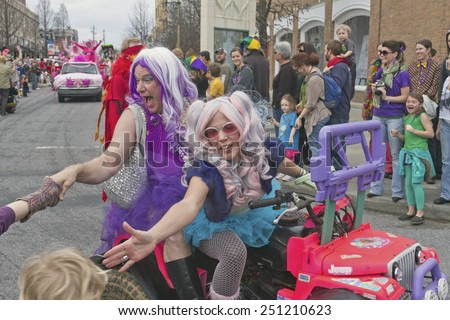 Asheville, North Carolina, USA - March 2, 2014:  People wearing colorful costumes give pageant style waves and shake the hands of happy spectators in the Mardi Gras parade in downtown Ashevile, NC - stock photo