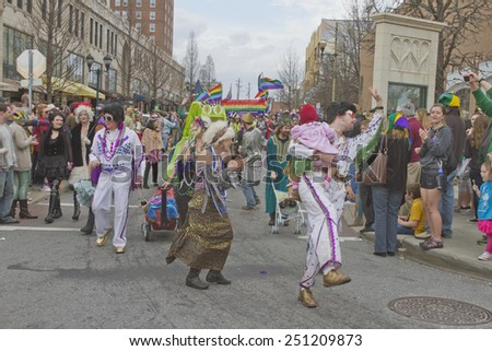 Asheville, North Carolina, USA - March 2, 2014:  Two Elvis characters along with people in other creative costumes frolic in the annual Mardi Gras Parade in downtown Asheville, North Carolina  - stock photo