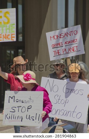 Asheville, North Carolina, USA - May 23, 2015: American activists protest Monsanto's genetically modified foods (GMOs) and hold protest signs in a nationwide event in downtown Asheville, NC  - stock photo