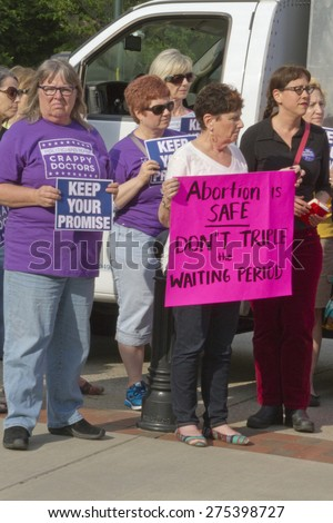 Asheville, North Carolina, USA - May 4, 2015:  Unhappy looking women hold signs protesting North Carolina's abortion Bill #465 which increases restrictions for women seeking abortions - stock photo