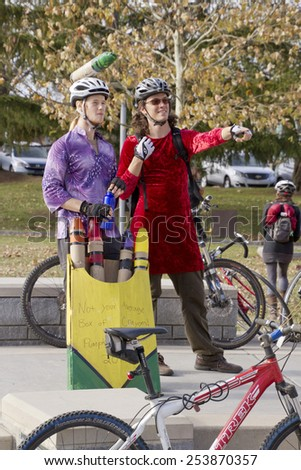 Asheville, North Carolina, USA - November 8, 2014: Two creatively costumed bicyclists wait for the Pumpkin Pedalers event ot begin on November 8, 2014 in downtown Asheville, NC  - stock photo
