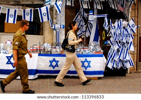 ASHKELON - APRIL 28:Israeli soldiers passing by a store in Israel that sells merchandise for the Israel national holiday of Independence Day on April 28 2006 in Ashkelon,Israel. - stock photo
