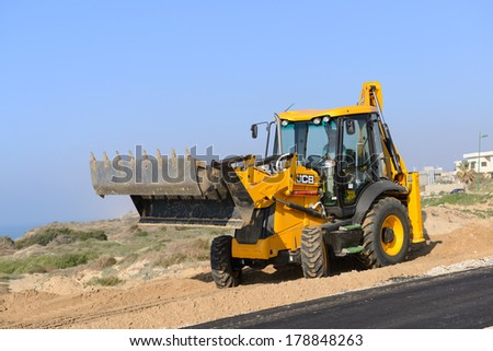 ASHKELON, ISRAEL- FEBRUARY 20, 2014:Wheel loader Excavator with backhoe  in the road building - stock photo