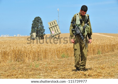 ASHKELON  - MAY 09: Iron Dome battery fighter  stands at attention to sound the siren in memory of the fallen IDF soldiers in Israel wars, on May 09 2011 in Askelon, Israel. - stock photo