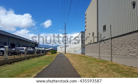 Ashpalt Path on Pearl Harbor Bike Path with Power lines above and Building surrounding trail on Oahu, Hawaii. - stock photo