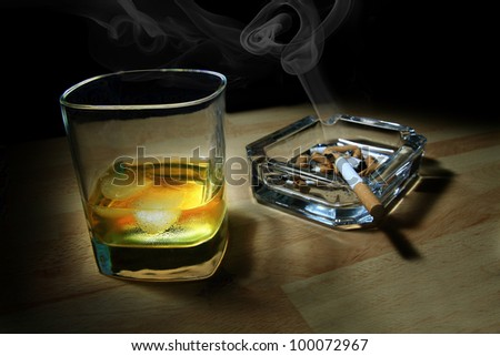 ashtray full of butts and glass of whiskey - stock photo