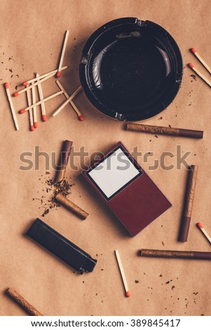 Ashtray, matches, a lighter and cigarettes scattered across the table - stock photo