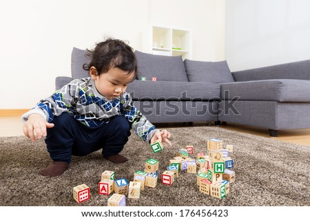 Asia baby boy concentrate on playing toy block - stock photo