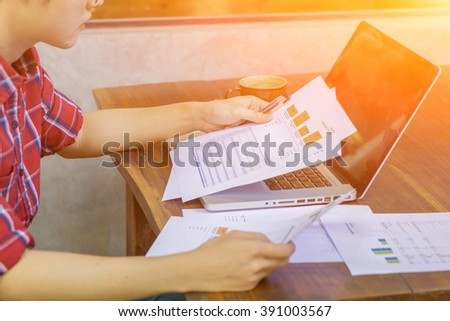 Asia business man analyzing investment charts with laptop on wood desk.Business people discussing the charts and graphs on desk.Signing, Contract, Forms. in office ,morning light ,selective focus. - stock photo