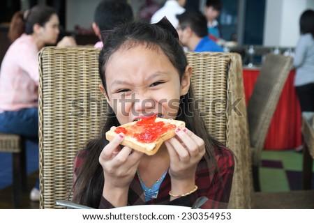 Asia children girl eat breakfast in restaurant. - stock photo