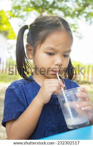 Asia little girl is dipping his tongue in the glass of milk - stock photo