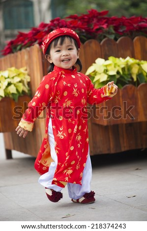 Asia little girl wears Vietnamese traditional long dress ( Ao Dai in Vietnamese) playing on playground by Dinh Tien Hoang street, Hanoi - stock photo
