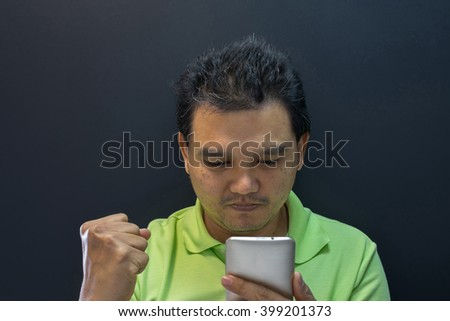 Asia man success and excited using smartphone on black background - stock photo