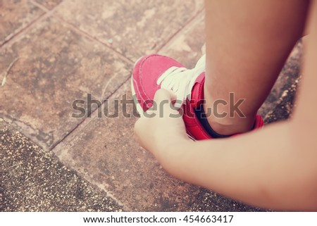 Asia woman runner tying shoelaces - stock photo