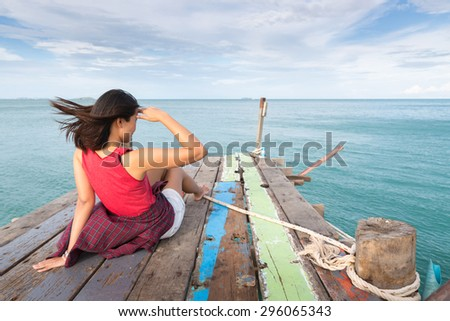 Asia woman traveler sitting and Look out of the sea on wooden bridge, Koh samet, Rayong, Thailand - stock photo