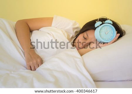 asia woman turning off the alarm clock. - stock photo