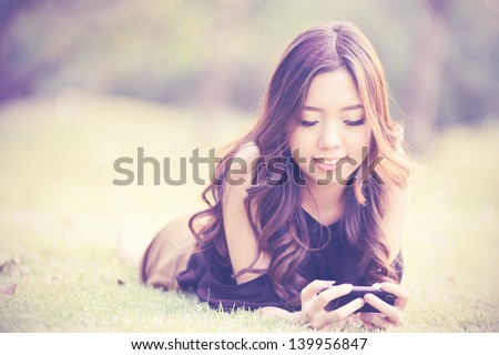 Asia women talking mobile phone in the park (Vintage Tone Style) - stock photo