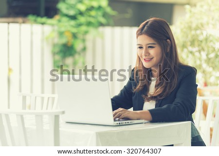 Asia young business woman sitting in cafe with laptop - stock photo