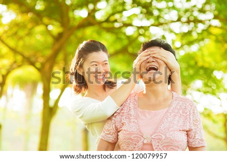 Asian adult daughter covering her senior mother eyes by hands at outdoor park - stock photo