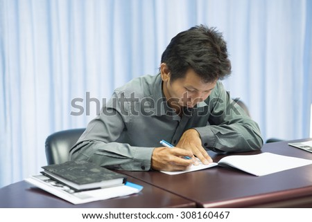 Asian adult education student struggles with test axam as anxiety as he takes an exam - stock photo