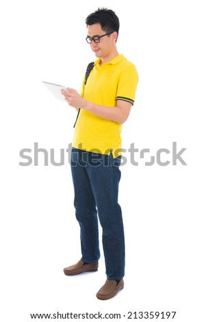 Asian adult student in casual wear with school bag using digital computer tablet pc standing isolated on white background. Asian male model. - stock photo