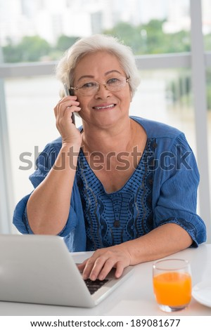 Asian aged woman talking on the phone while using notebook - stock photo