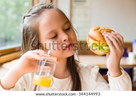 Asian American girl with orange juice and hamburger - stock photo